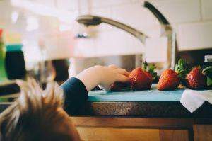 Bambino mentre è in casa mentre prende un frutto
