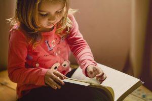 Bambina bionda seduta per terra mentre sfoglia un libro, passatempo, giochi in casa