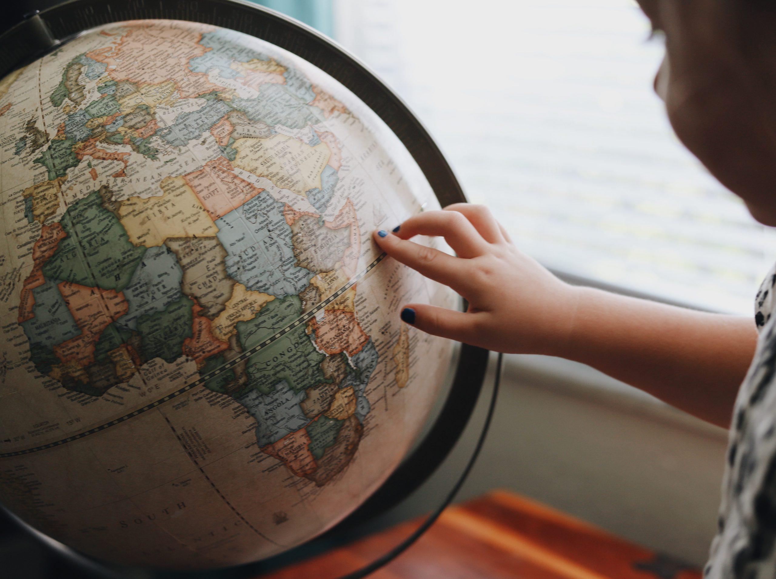 junia pharma giochi educativi bambini - mano di bambina che indica il mappamondo