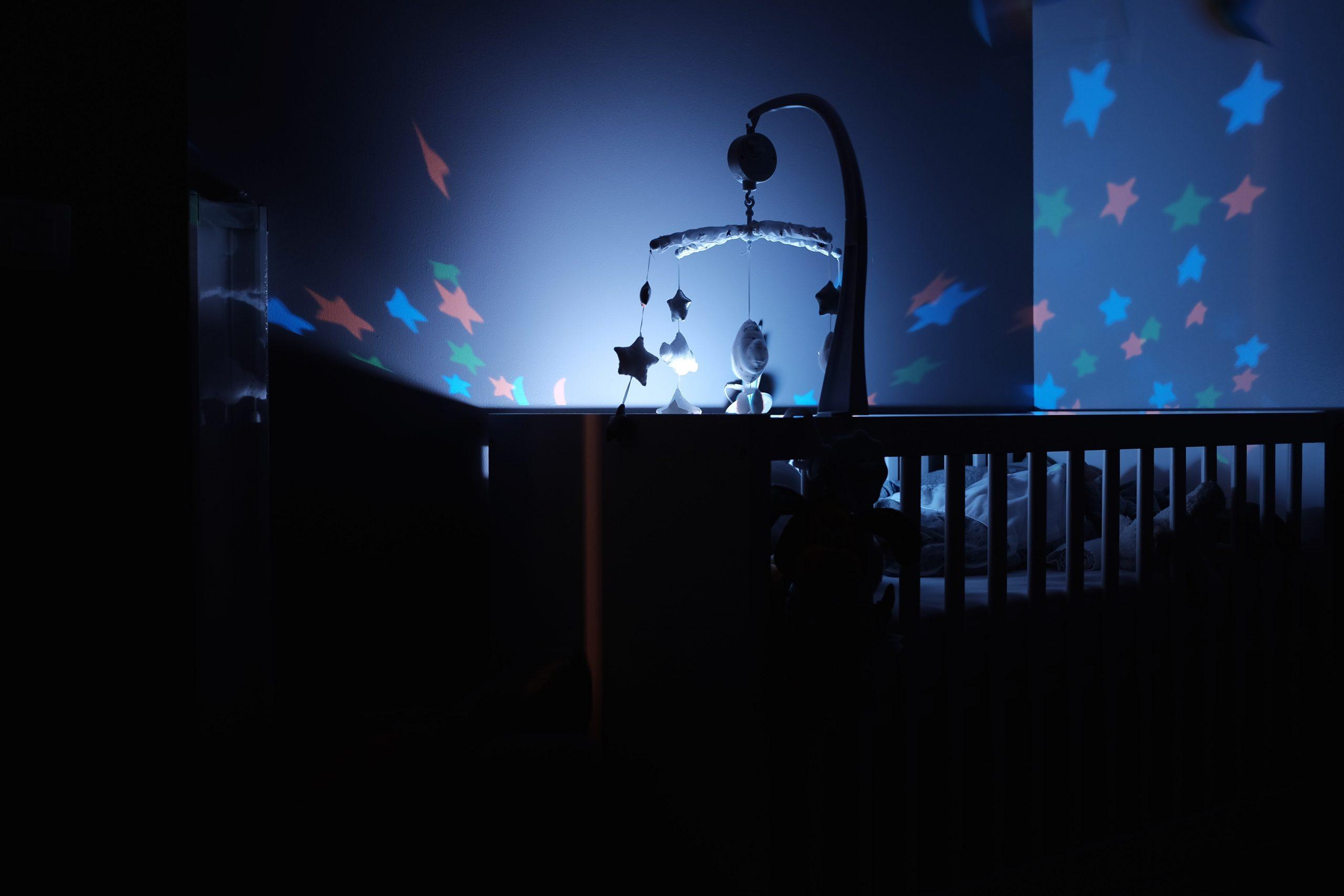 a che ora devono dormire i bambini - stanza di bambino al buio con culla illuminata da stelline luminose