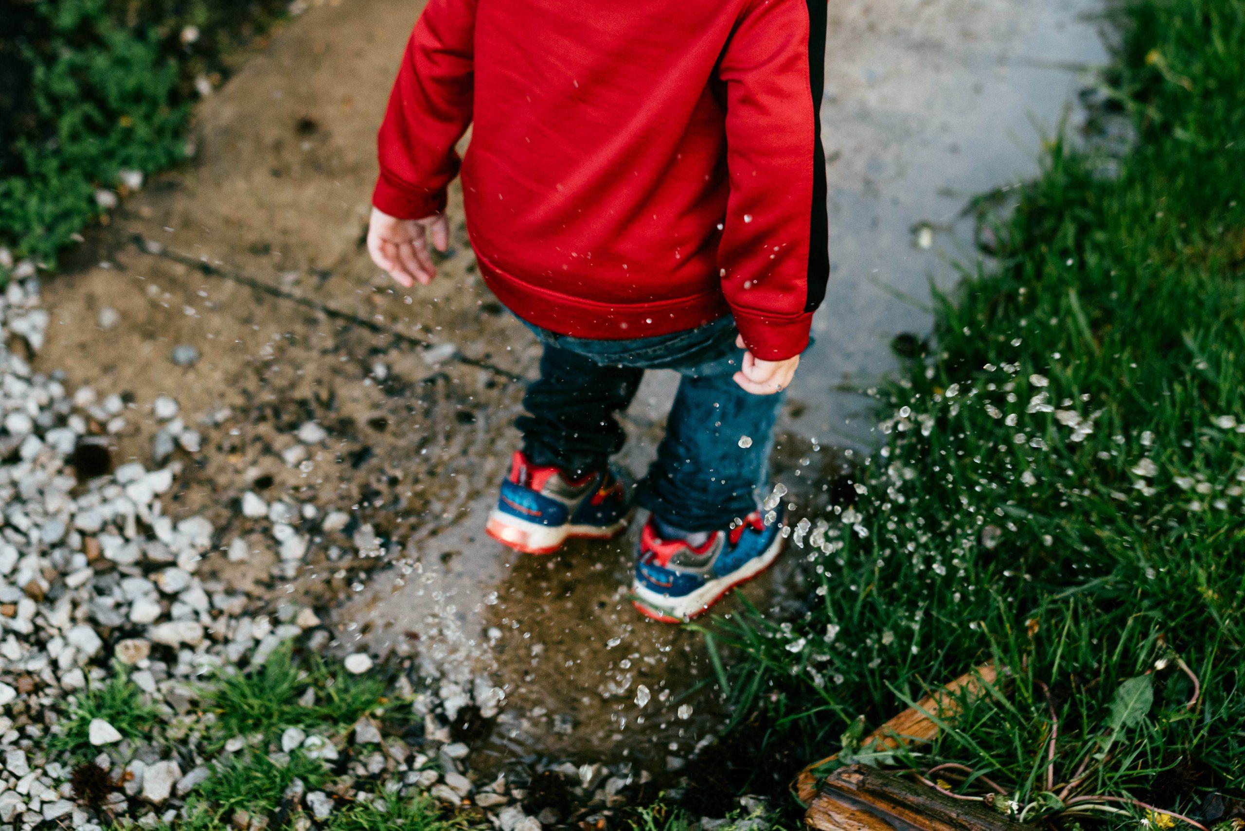 bambino che salta in una pozzanghera