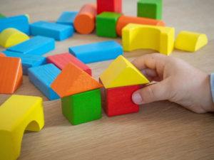 manina di bambino che gioca con mattoncini colorati - giochi educativi - costruzioni di legno