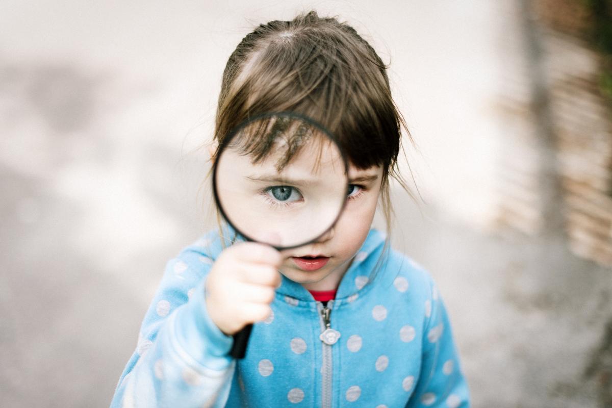 junia pharma - bambina con lente di ingrandimento di fronte all'occhio